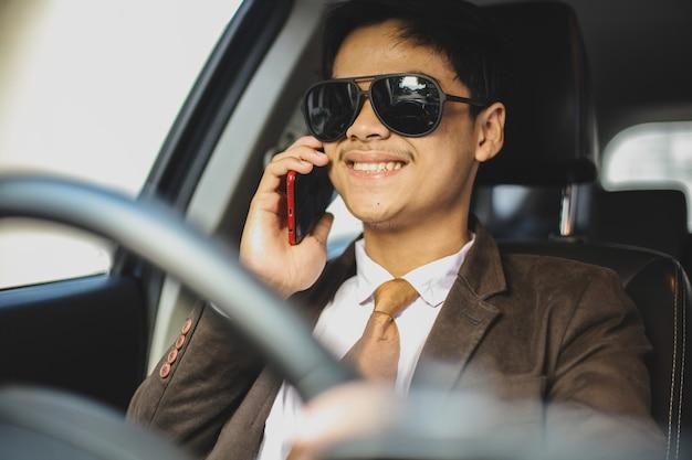 Un uomo d'affari asiatico sorridente con gli occhiali da sole sta guidando un'auto mentre conversa sullo smartphone