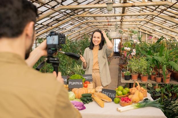 Sorridente blogger asiatico di alimenti naturali in piedi al tavolo con alimenti biologici e fare video dalla serra insieme all'operatore della telecamera