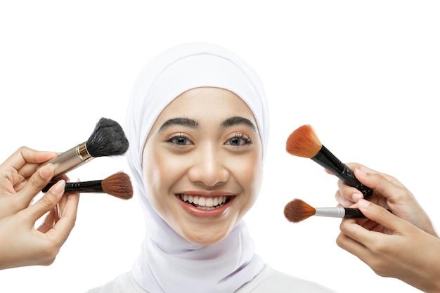 Sorridente donna asiatica hijab che indossa un velo bianco con molti pennelli