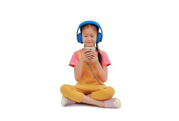 Sorridente bambina asiatica che indossa le cuffie e si diverte con lo smartphone seduto sul bianco