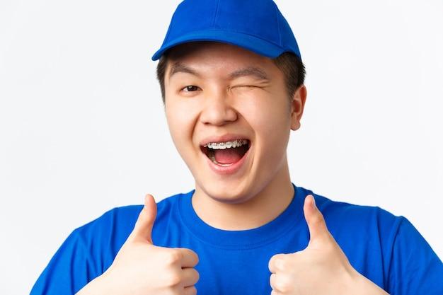 Sorridente corriere maschio asiatico in uniforme blu