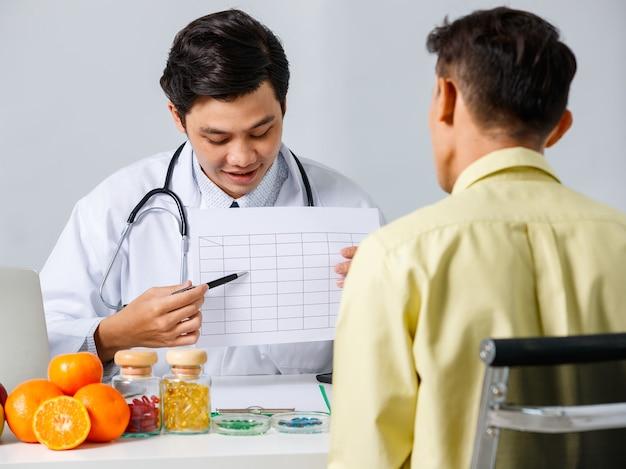 Sorridente dietista maschio asiatico che mostra il grafico al paziente mentre spiega la soluzione per la dieta sana su sfondo bianco