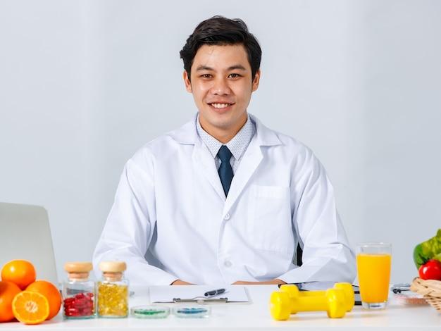 Sorridente nutrizionista maschio asiatico seduto al tavolo con frutta fresca assortita e guardando la telecamera mentre mostra il concetto di dieta sana
