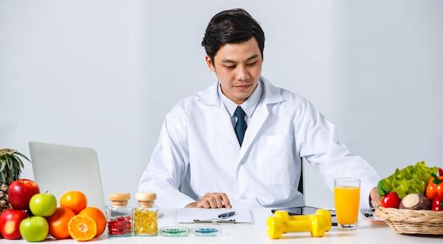 Sorridente nutrizionista maschio asiatico seduto al tavolo con frutta fresca assortita e guardando il computer labelt mentre mostra il concetto di dieta sana