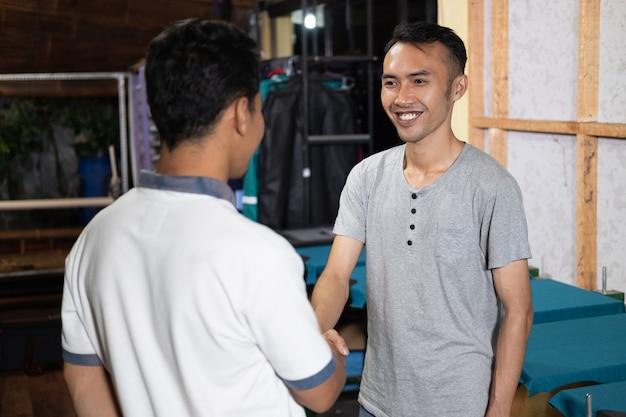 Sorridente proprietario maschio asiatico si stringono la mano quando si incontrano i clienti presso l'ufficio di serigrafia