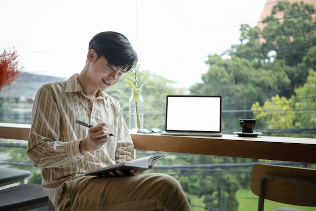 Sorridente uomo asiatico freelance seduto in una moderna caffetteria e scrivendo nuove idee sul taccuino.