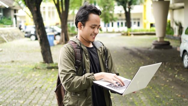 Sorridente uomo asiatico che indossa uno zaino con un computer portatile