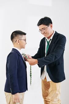 Uomo di mezza età asiatico sorridente che aiuta il figlio di tween ad aggiustare la cravatta quando si prepara per la celebrazione