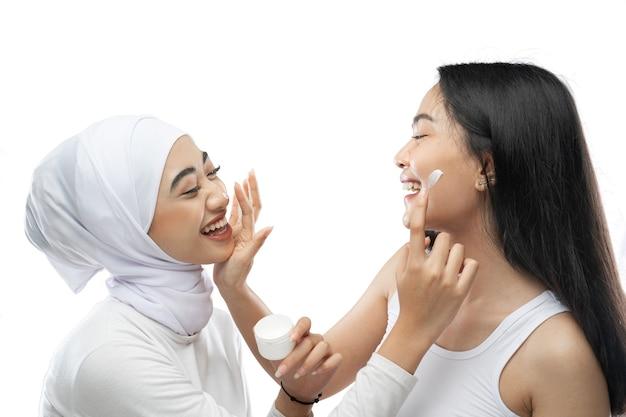 Sorridente migliore amica musulmana asiatica che applica la crema per il viso con le mani delle dita