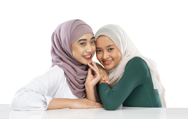 Sorridente migliore amica musulmana asiatica davanti alla telecamera