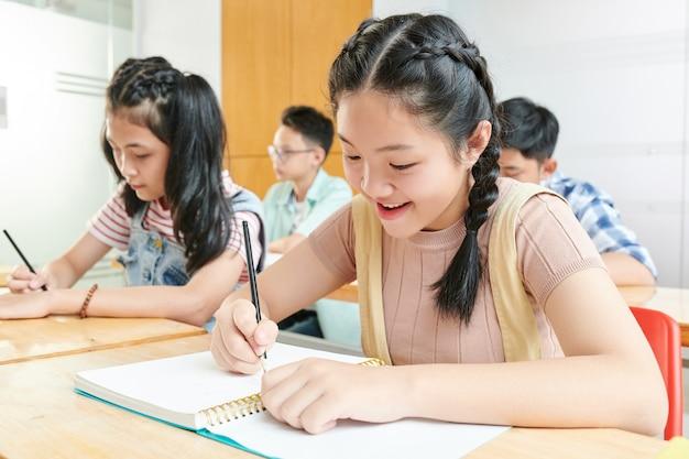 Sorridenti scolari asiatici che scrivono nei libri di testo in classe
