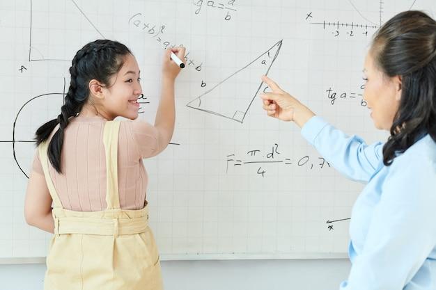 Sorridente studentessa asiatica tornando a parlare insegnante durante la scrittura dell'equazione sulla lavagna