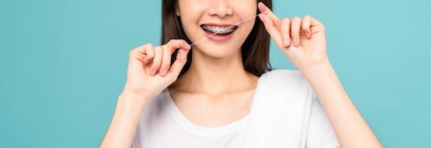 Sorridente donna asiatica che pulisce bretelle sui denti con filo interdentale su sfondo blu, concetto di igiene orale e assistenza sanitaria