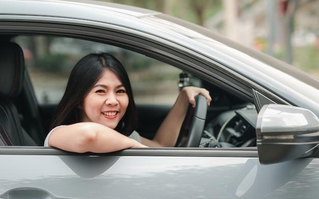 Donna asiatica sorridente che conduce la sua nuova automobile