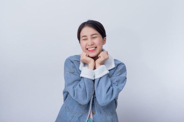 Sorridente donna asiatica sentirsi felice su sfondo bianco con copia spazio