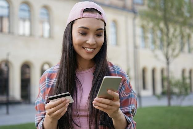 Donna asiatica sorridente che utilizza il telefono cellulare che tiene la carta di credito che acquista online