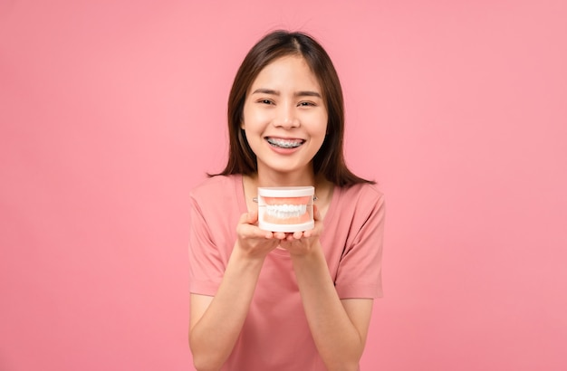 Sorridente donna asiatica che indossa bretelle che tengono il modello del dente su sfondo rosa, concetto di igiene orale e assistenza sanitaria