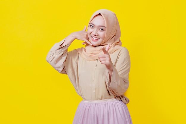 Sorridente donna asiatica che indossa l'hijab con il dito puntato su di te con la chiamata di qualcuno espressione isolata su sfondo giallo chiaro banner