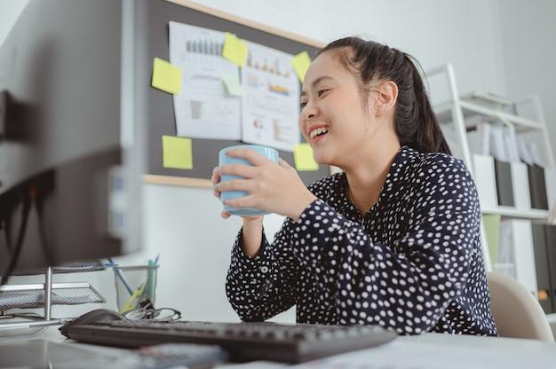 Sorridente donna asiatica che indossa una camicia a pois con una tazza di caffè o tè vicino al computer sul posto di lavoro