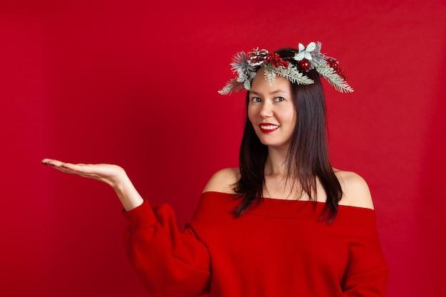 Sorridente donna asiatica con uno spazio vuoto nel palmo della mano per la pubblicità