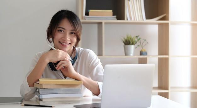 Donna asiatica sorridente che lavora alla scrivania con libri e computer portatile.