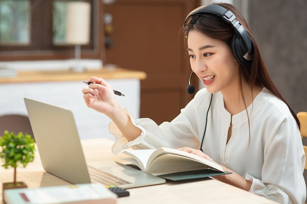 La giovane femmina asiatica sorridente che utilizza la cuffia avricolare che esamina lo schermo del laptop ascolta e che apprende i corsi in linea. Foto Premium