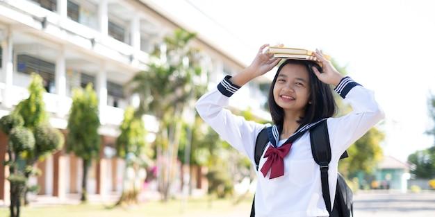 Sorridente ragazza asiatica indossa uniforme in piedi a scuola