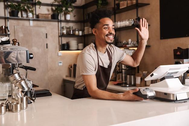 Sorridente attraente barista africano in piedi dietro il bancone della caffetteria, salutando i clienti
