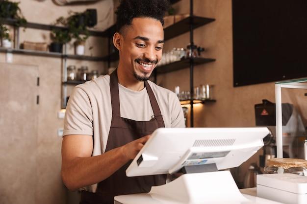 Sorridente attraente barista africano in piedi dietro il bancone della caffetteria