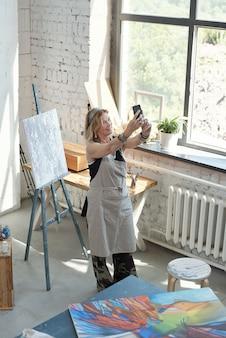 Artista attraente sorridente in grembiule che prende selfie sulla propria immagine in studio d'arte