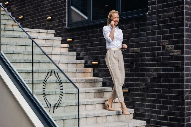 Signora alla moda bionda attraente sorridente scendendo le scale e parlando al telefono.
