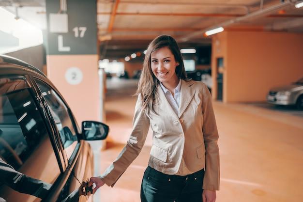 Porta di automobile casuale astuta astuta vestita castana attraente sorridente al garage pubblico.