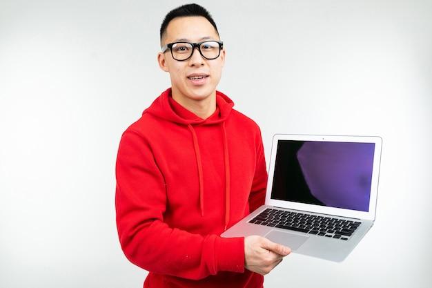 Sorridente uomo attraente brunetta dimostra uno schermo di computer portatile vuoto con mockup nelle sue mani su uno sfondo bianco studio.