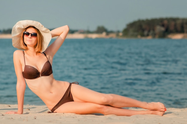 Sorridente ragazza esile caucasica attraente in occhiali e cappello sulla spiaggia, sdraiata sulla sabbia dorata. ricreazione e coccole in riva al mare (oceano, fiume, lago) in estate e nelle giornate di sole.