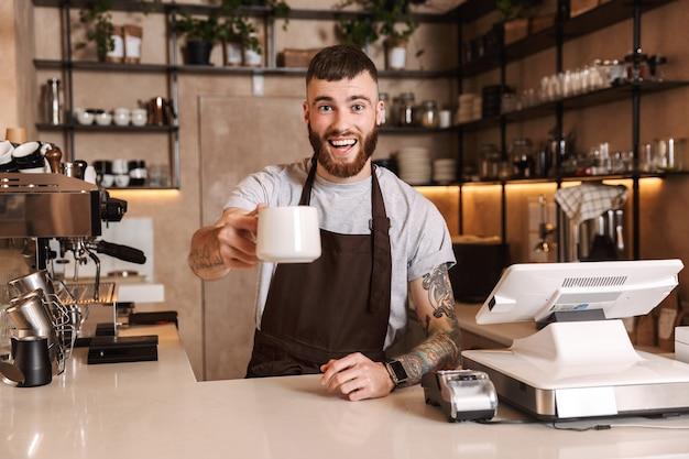 Sorridente uomo attraente barista in piedi dietro il bancone della caffetteria, mostrando una tazza di caffè