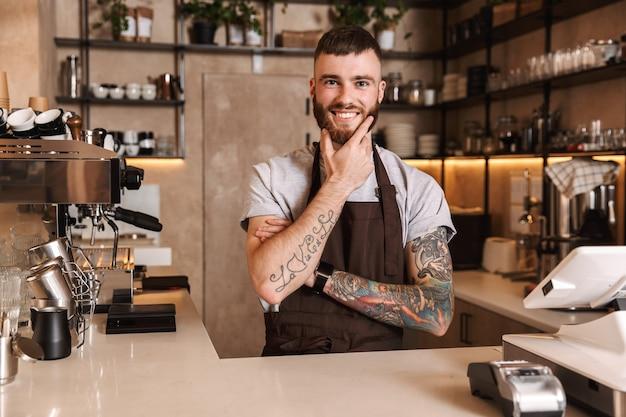 Sorridente barista uomo attraente in piedi dietro il bancone della caffetteria
