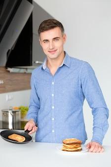 Sorridente uomo attraente in camicia blu che cucina e prepara frittelle in cucina