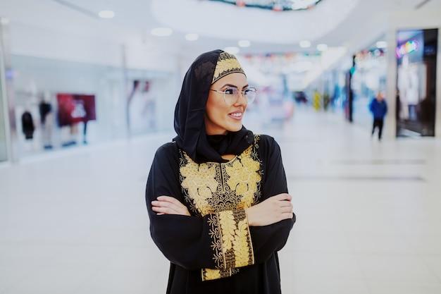 Sorridente attraente donna musulmana in abbigliamento tradizionale in piedi nel centro commerciale con le braccia incrociate e guardando lontano.