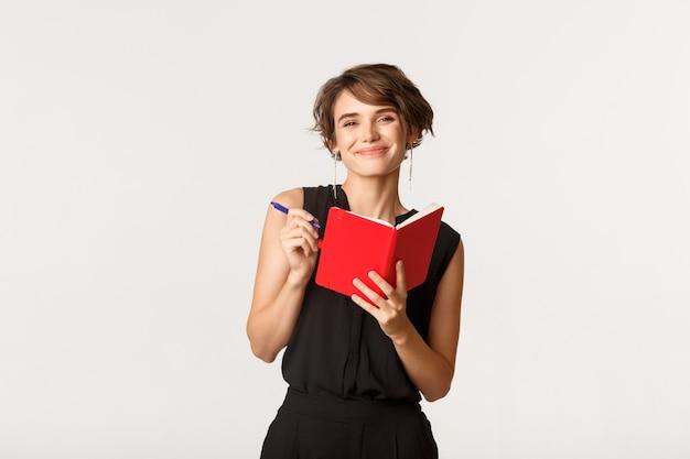 La donna attraente sorridente che prende le note nel pianificatore, prepara il programma di lavoro nel taccuino, levandosi in piedi sopra il bianco.