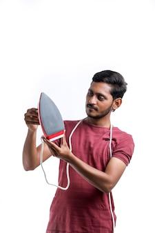 Sorridente giovane casalingo attraente in grembiule tenere in mano il ferro mentre si fanno i lavori domestici isolato su sfondo giallo ritratto in studio. concetto di pulizia.