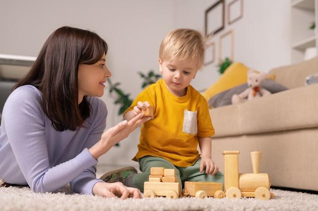 Sorridente attraente giovane madre sdraiata sul tappeto e dando blocco di legno al figlio mentre gli insegna a impilare blocchi giocattolo
