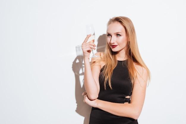 Sorridente attraente giovane donna in piedi e bere champagne su sfondo bianco