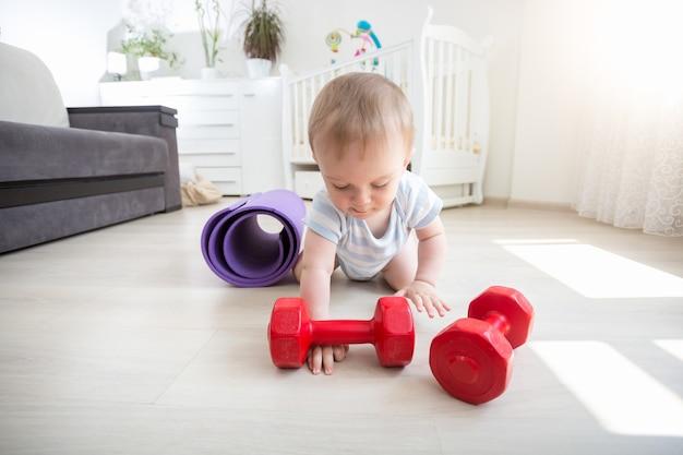 Neonato sorridente che gioca con i manubri sul pavimento a casa
