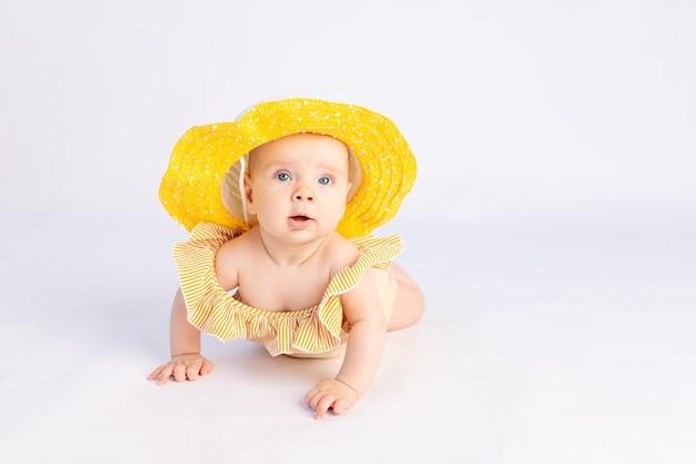 Sorridente bambina di 6 mesi in costume da bagno e cappello da sole sdraiato su uno sfondo bianco isolato, spazio per il testo