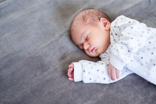 Neonata sorridente sdraiata su un letto che dorme sulle lenzuola blu.