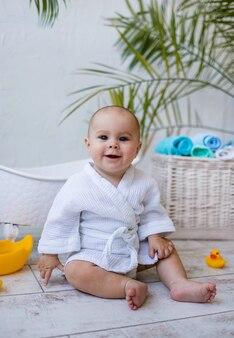 Una bambina sorridente con un accappatoio bianco si siede con anatre di giocattoli di gomma accanto a un bagnetto
