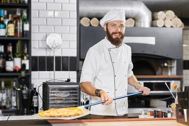 Panettiere sorridente che porta tunica bianca che tiene pala metallica lunga con pizza.