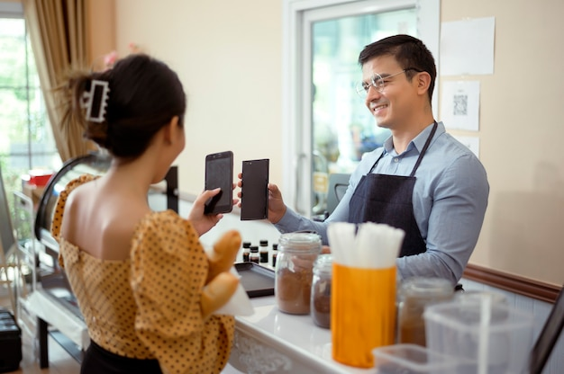 Barista sorridente che dà il pagamento online al cliente, paga l'ordine in un bar