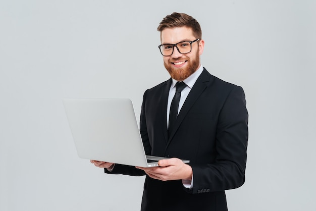 Sorridente uomo d'affari barbuto con gli occhiali e vestito nero che tiene il laptop