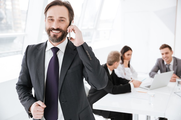 Uomo d'affari barbuto sorridente che parla al telefono in ufficio con i colleghi